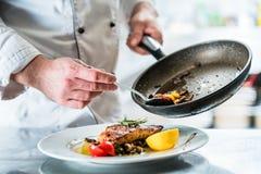 Еда отделкой шеф-повара в его кухне ресторана стоковая фотография