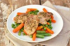 Еда от филе мяса свинины с специями и морковами младенца весеннего овоща, горохами и зелеными фасолями на белой плите на деревянн Стоковые Изображения RF
