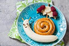 Еда потехи Плюшка циннамона с бананом выглядеть как улитка стоковое фото