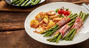 Еда спаржи, poscuitto и картошек на плите Стоковая Фотография RF