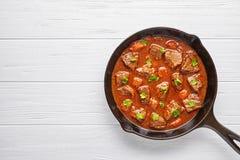 Еда супа тушёного мяса мяса говядины гуляша традиционная домодельная венгерская с пряной подливкой в skillet лотка литого железа Стоковые Изображения RF