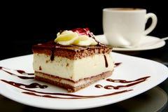 Еда сладостного сметанообразного шоколадного торта с кофе