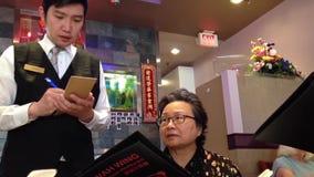 Еда людей приказывая внутри китайского ресторана