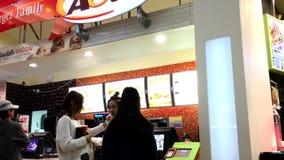 Еда людей приказывая внутри ресторана A&W внутри торгового центра Coquiltam сток-видео
