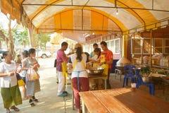 Еда Offerring к людям на монастыре спетом Tha Стоковая Фотография