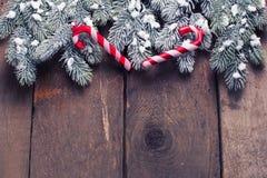 Елевые ветви и декоративная тросточка конфеты на постаретом деревянном backgr Стоковые Изображения