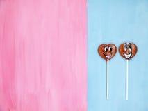 2 леденца на палочке на розовой и голубой предпосылке человек влюбленности поцелуя принципиальной схемы к женщине красный цвет по Стоковая Фотография