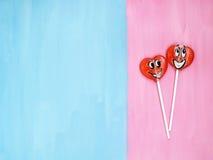 2 леденца на палочке на розовой и голубой предпосылке человек влюбленности поцелуя принципиальной схемы к женщине красный цвет по Стоковое Изображение