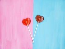 2 леденца на палочке на розовой и голубой предпосылке человек влюбленности поцелуя принципиальной схемы к женщине красный цвет по Стоковые Фотографии RF