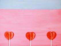 3 леденца на палочке на розовой и голубой предпосылке Стоковое Фото