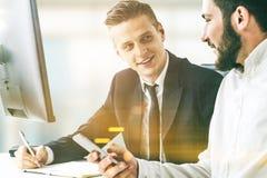 2 делового партнера работая в офисе с smartphone Стоковое Фото