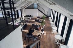 2 делового партнера сидя на столе в офисе и взаимодействуя Стоковые Фотографии RF