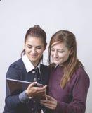 2 делового партнера, смотря кто-то смешное видео в таблетке и усмехаться изолировано Стоковое Изображение RF