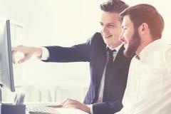 2 делового партнера указывая на экран компьютера Стоковое Фото