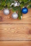 Ель рождества с снегом и безделушки на деревенской деревянной доске Стоковые Фотографии RF