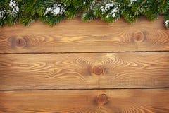 Ель рождества с снегом на деревенской деревянной доске Стоковые Фото