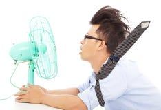 Жара лета, вентиляторы пользы бизнесмена, который нужно охладить вниз Стоковые Изображения