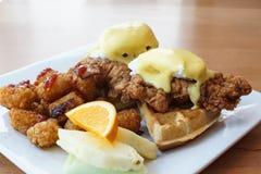 Жареная курица и вафли с яйцами Венедиктом на верхней части стоковое фото