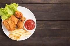 Жареная курица, кетчуп и фраи на деревянной предпосылке Быстро-приготовленное питание Стоковые Изображения