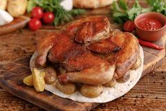 Жареная курица на деревянной предпосылке с гарнировать испеченной молодой картошки Цыпленок табака деревенский Стоковая Фотография