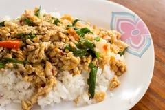 Жареные рисы с базиликом на белой плите на деревянном столе. Стоковое Изображение RF