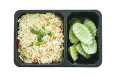Жареные рисы с яичком и отрезанным огурцом в черном пластичном подносе изолированном на белой предпосылке Стоковая Фотография RF