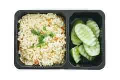 Жареные рисы с яичком и отрезанным огурцом в черном пластичном подносе изолированном на белой предпосылке Стоковые Изображения