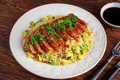 Жареные рисы яичка китайского стиля с отрезанным филе свинины на деревянном столе Стоковое фото RF