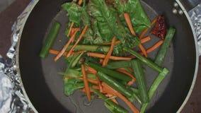 Жарить свежих овощей в лотке на пламени Open видеоматериал