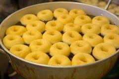 Жарить donuts в смазанных лотках стоковое изображение