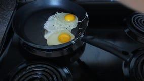 Жарить eggs в лотке на черной плите сток-видео