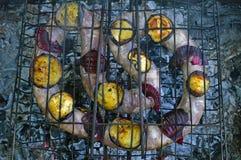 Жарка сосиски на горящих тлеющих углях outdoors на пикнике стоковые изображения rf