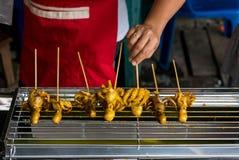 Жарят свежий кальмара на протыкальниках уличным торговцем в тайском рынке ночи улицы тип еды тайский стоковые изображения rf