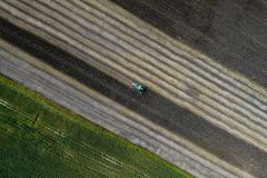 Жатка жмет урожай в поле рядом с зеленым полем с мозолью Украина вид с воздуха Стоковая Фотография