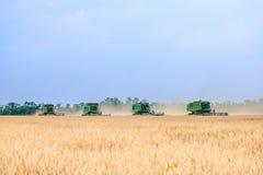 4 жатки зернокомбайна John Deere жать пшеницу в поле Стоковое Фото
