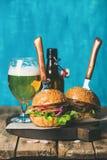 Жалуйтесь бургеры с кудрявыми беконом, овощами и пивом пшеницы Стоковые Изображения