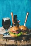 Жалуйтесь бургеры с кудрявым беконом, овощами и темным пивом Стоковое Изображение