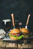 Жалуйтесь бургер с кудрявыми беконом и стеклом темного пива Стоковое Изображение RF