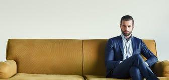 Ждать встречу Хорошо одетый молодой и успешный бизнесмен сидит на софе на офисе и ждет кто-нибудь стоковое фото rf