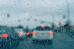 Ждать на соединении движения для зеленого света во время дождливого дня; стоковая фотография