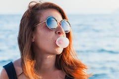 Жевательная резинка молодой женщины дуя Стоковая Фотография RF