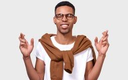 Желательный молодой Афро-американский человек обхватывает зубы, повышения пальцы пересекли, делает желаемое желание стоковое изображение rf