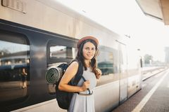 Железная дорога и перемещение темы Женщина портрета молодая кавказская при зубастая улыбка стоя на предпосылке поезда вокзала с b стоковое изображение rf