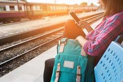 Железная дорога путешественника и рюкзака молодой женщины ждать на вокзале, молодой женщине сидя с использованием smartphone на в стоковое изображение