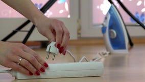 Железная проволока штепсельной вилки руки женщины эконома к переключателю расширения электричества видеоматериал