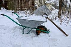 Железная тачка с снегом и лопаткоулавливатель в сугробе Стоковые Изображения RF