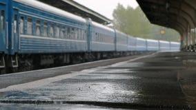Железнодорожная станция Поезд на дороге Оно идет дождь, падает падение на конец-вверх асфальта сток-видео