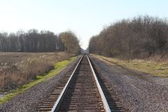 Железнодорожные пути идут в расстояние на сумраке Стоковые Изображения