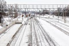 Железнодорожный вокзал в зиме, на заднем плане люди очищает снег стоковое изображение