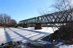 Железнодорожный мост над замороженным рекой зимы Стоковые Изображения